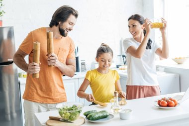 beautiful young family playing music with kitchenware and having fun at kitchen