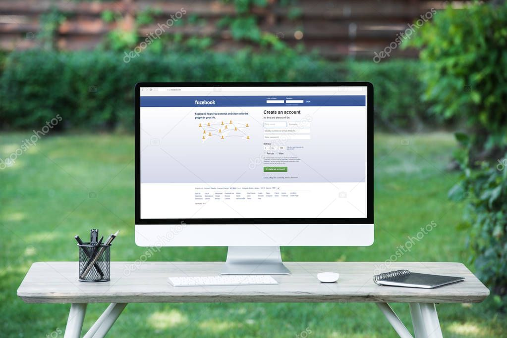 selective focus of computer with facebook website at table outdoors