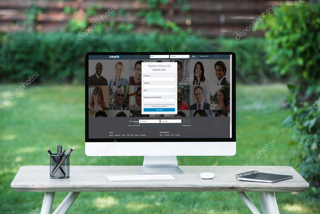 selective focus of computer with linkedin website at table outdoors