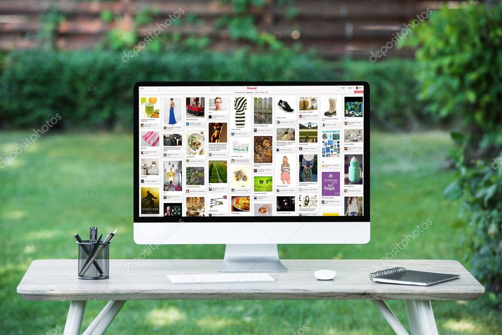 selective focus of computer with pinterest website at table outdoors