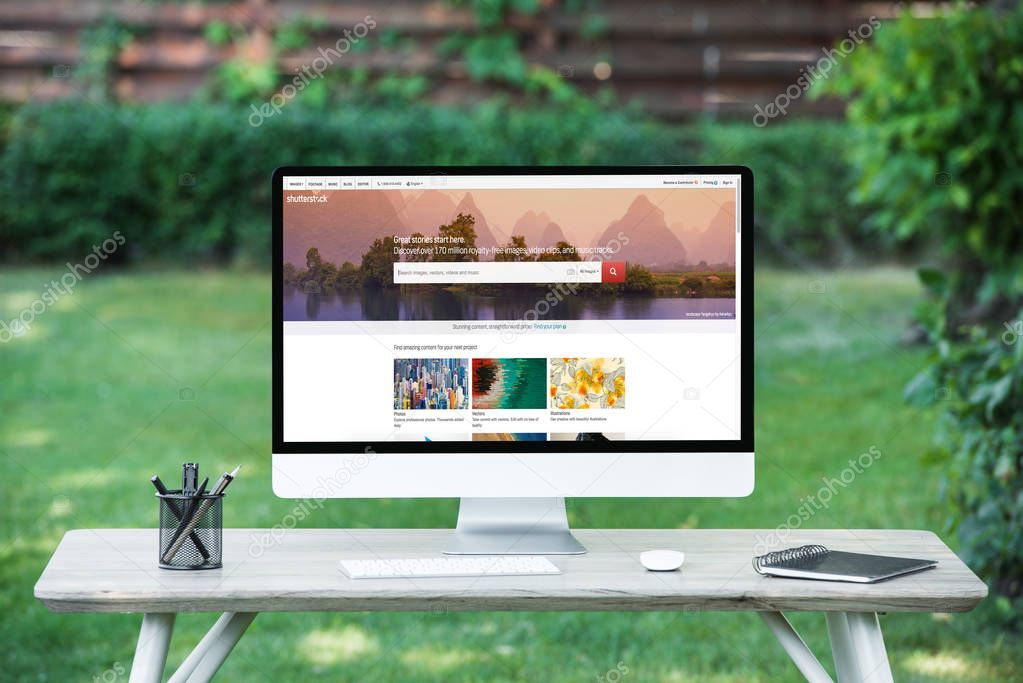 selective focus of computer with shutterstock website at table outdoors