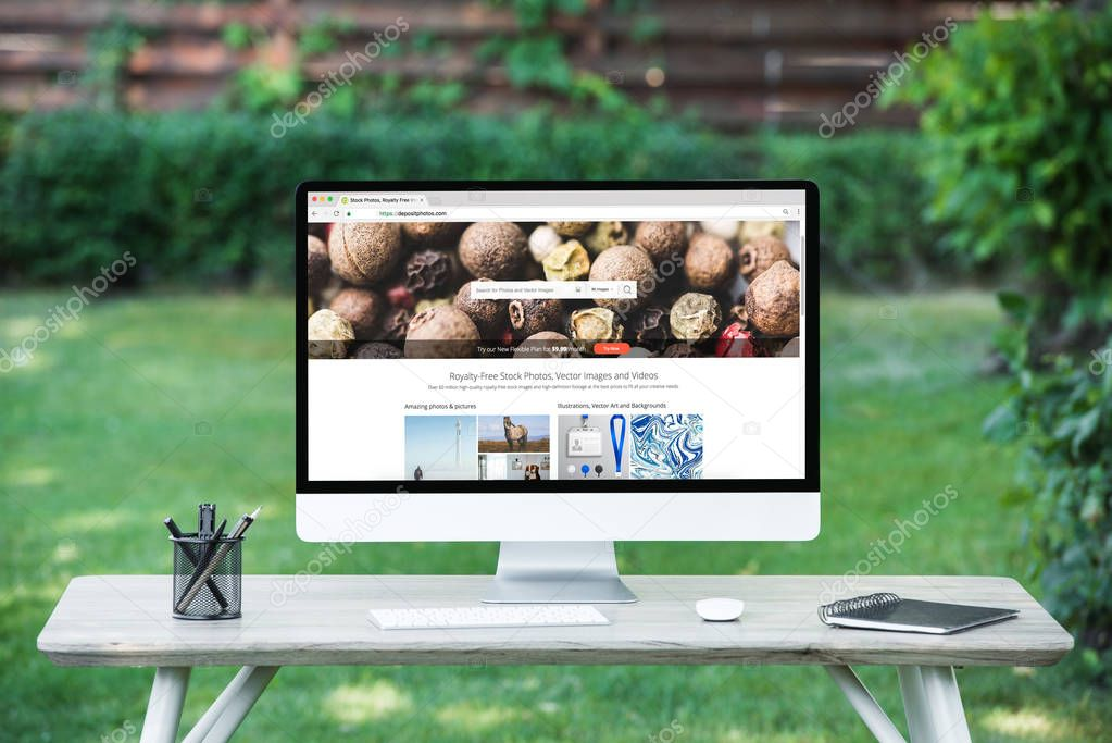 selective focus of computer monitor with depositphotos.com website at table outdoors