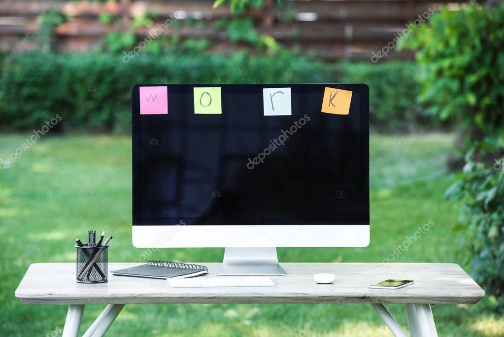 selective focus of textbook, smartphone, computer and stick it notes with lettering work hanging on computer monitor at table outdoors