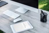 Selektivní fokus digitální tablet s vk.com blokované stránky a počítače s černou obrazovkou u stolu venku