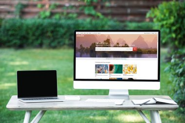 selective focus of laptop with blank screen computer with shutterstock website at table outdoors