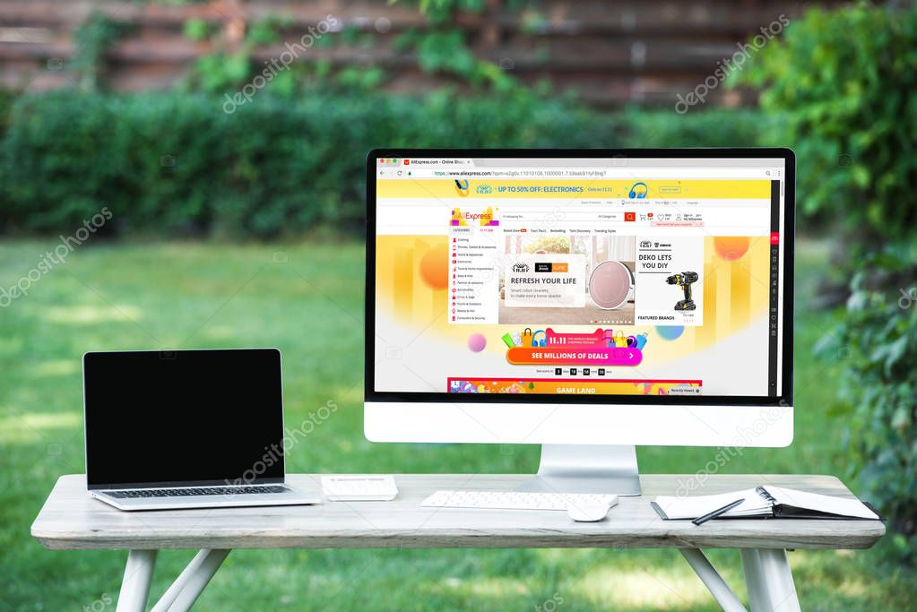 selective focus of laptop with blank screen computer with aliexpress website at table outdoors
