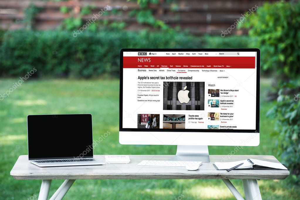 selective focus of laptop with blank screen computer with bbc news website at table outdoors