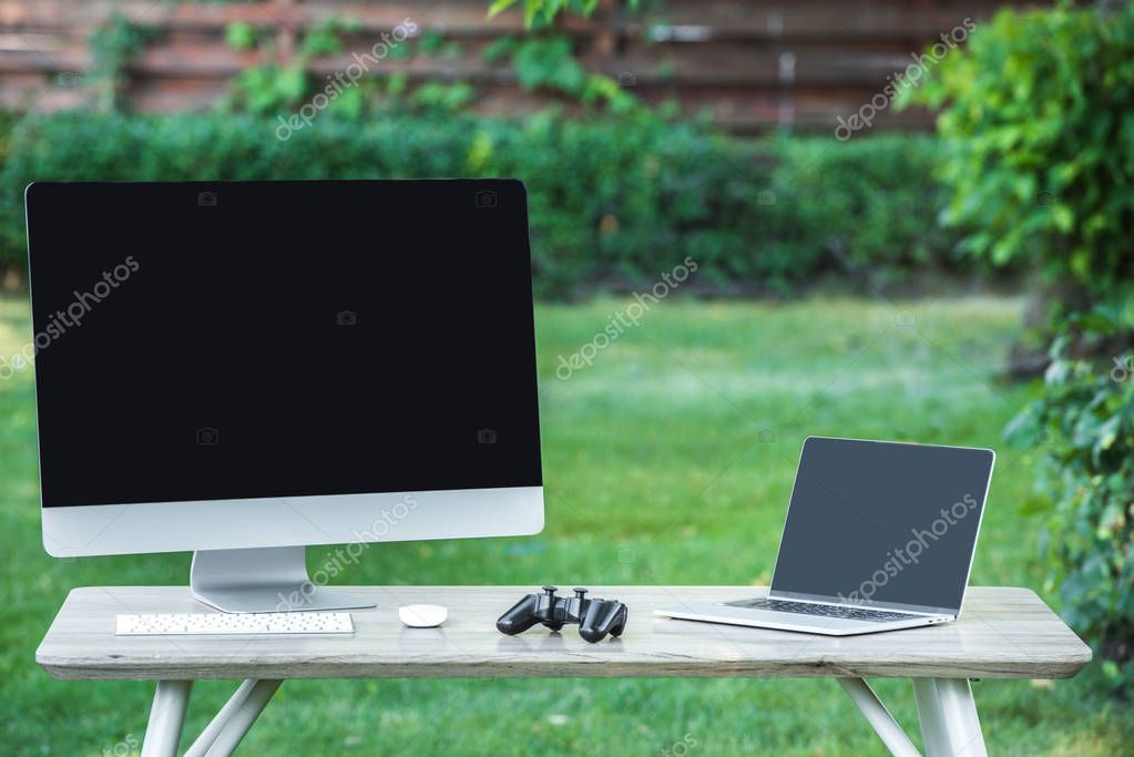 selective focus of joystick, computer and laptop with blank screens on table outdoors