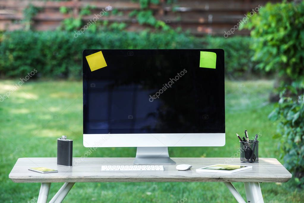 selective focus of flask, digital tablet, computer with blank screen, stick it notes and smartphone on table outdoors