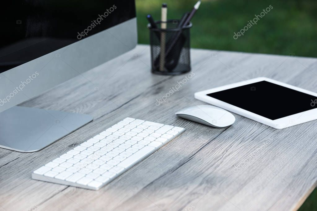selective focus of digital tablet and computer with blank screens at table outdoors