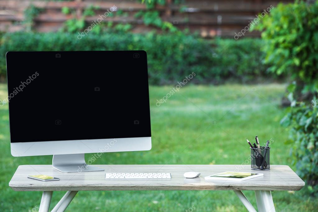 selective focus of smartphone, digital tablet and computer with blank screen at table outdoors