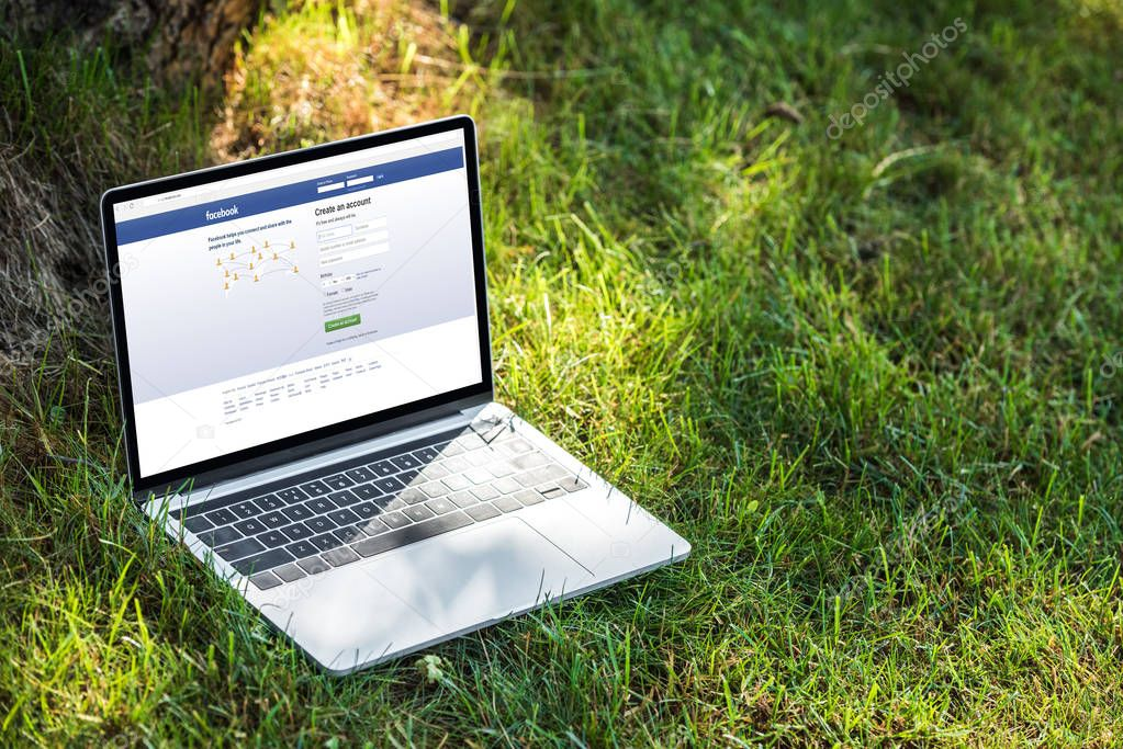 close up view of laptop with facebook website on grass outdoors