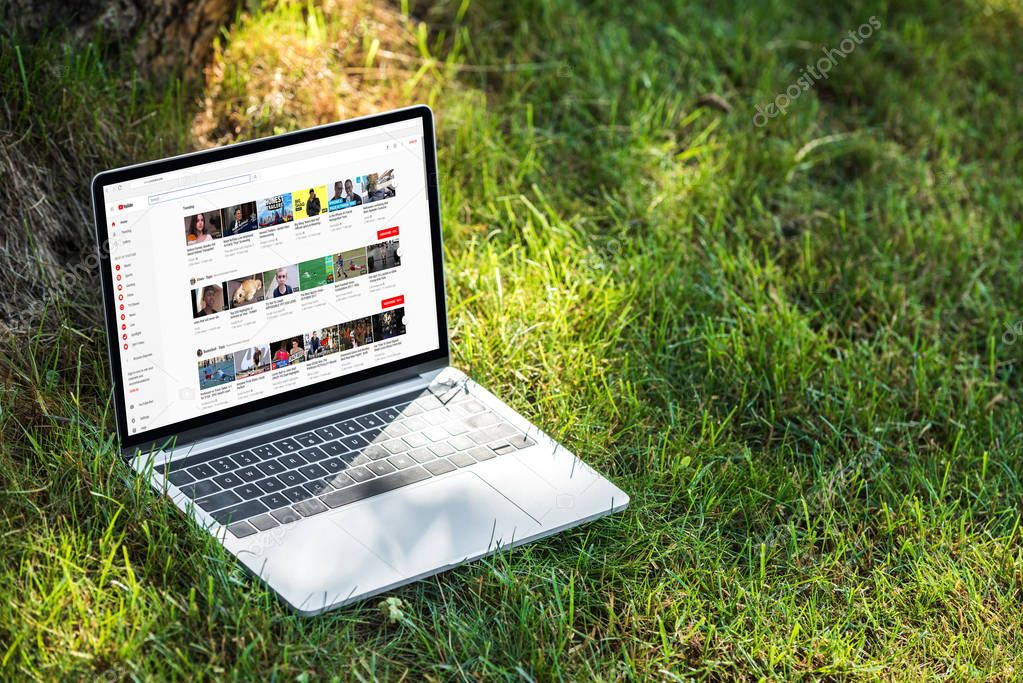 close up view of laptop with youtube website on grass outdoors