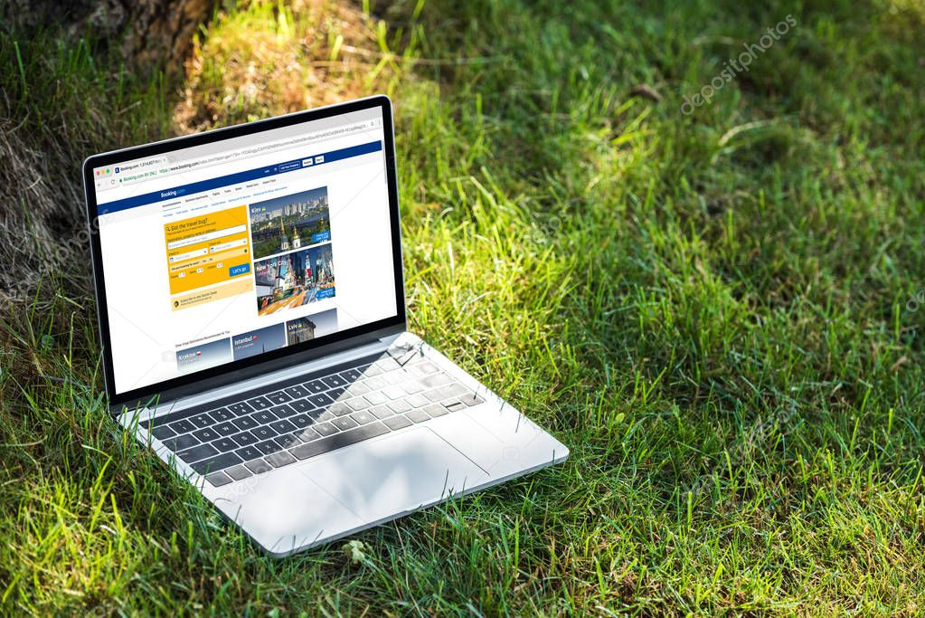 close up view of laptop with booking.com website on grass outdoors