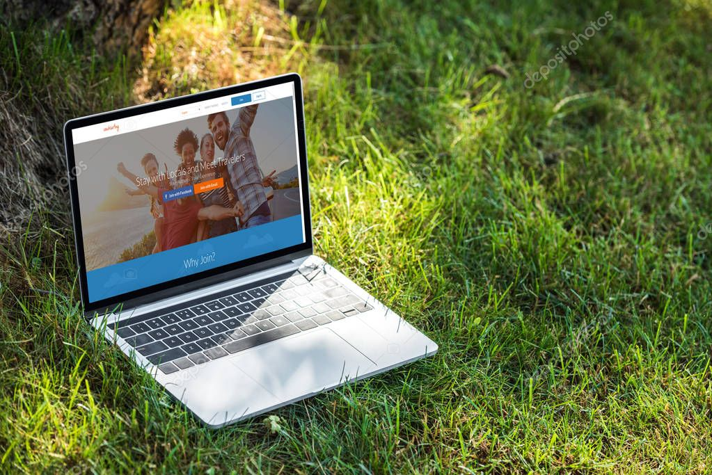 close up view of laptop with couchsurfing website on grass outdoors