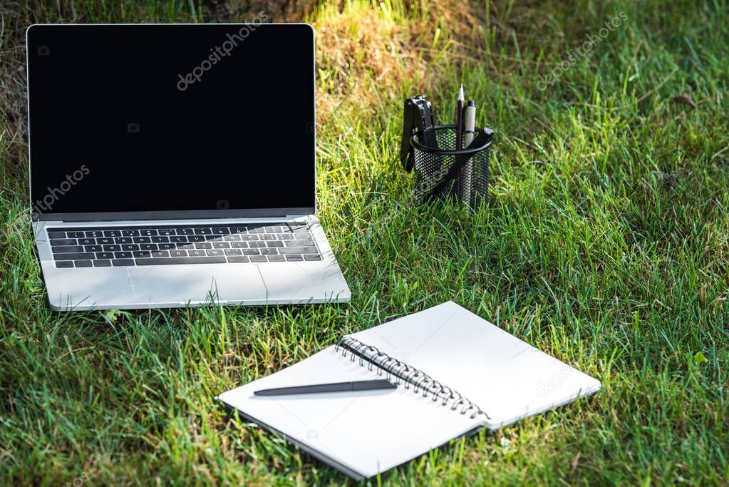 close up view of laptop with blank screen and empty textbook with pen on grass outdoors