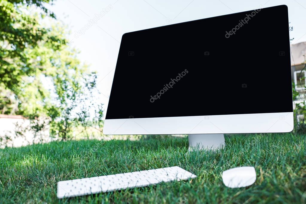 selective focus of computer with blank screen on grass outdoors