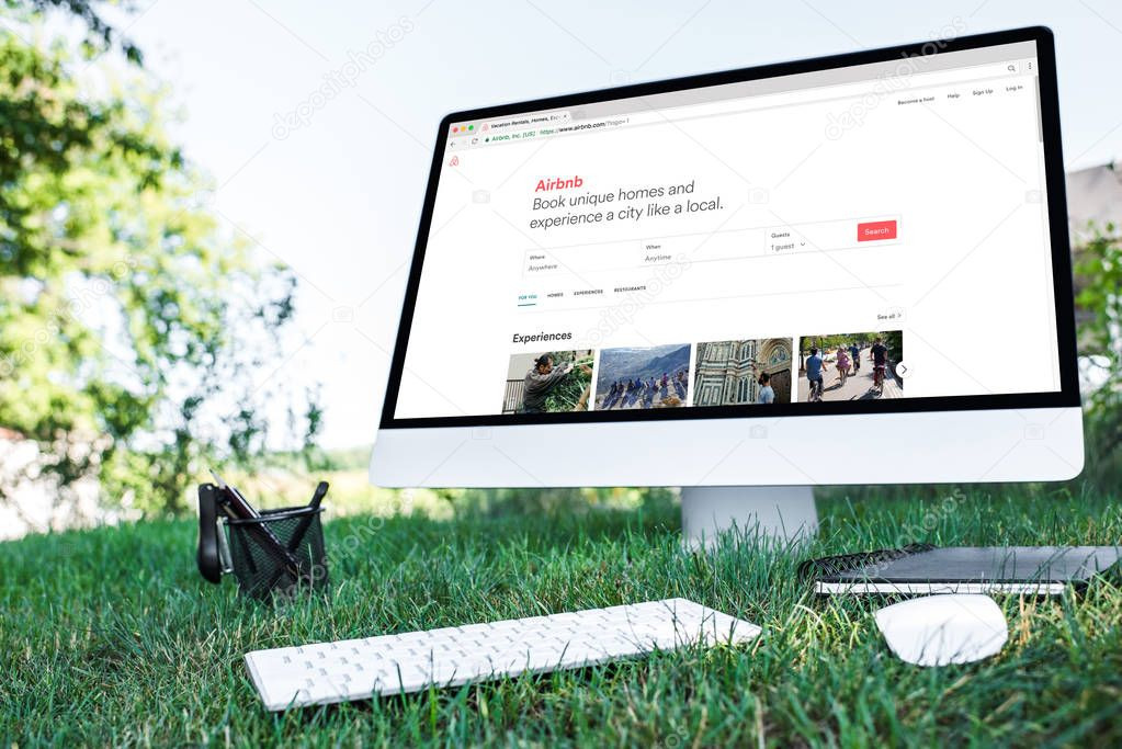 selective focus of textbook and computer with airbnb website on grass outdoors