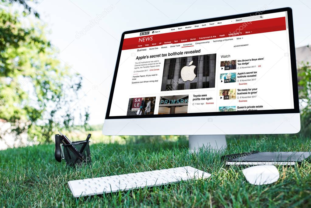 selective focus of textbook and computer with bbc news website on grass outdoors