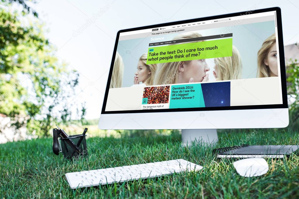 selective focus of textbook and computer with bbc science website on grass outdoors