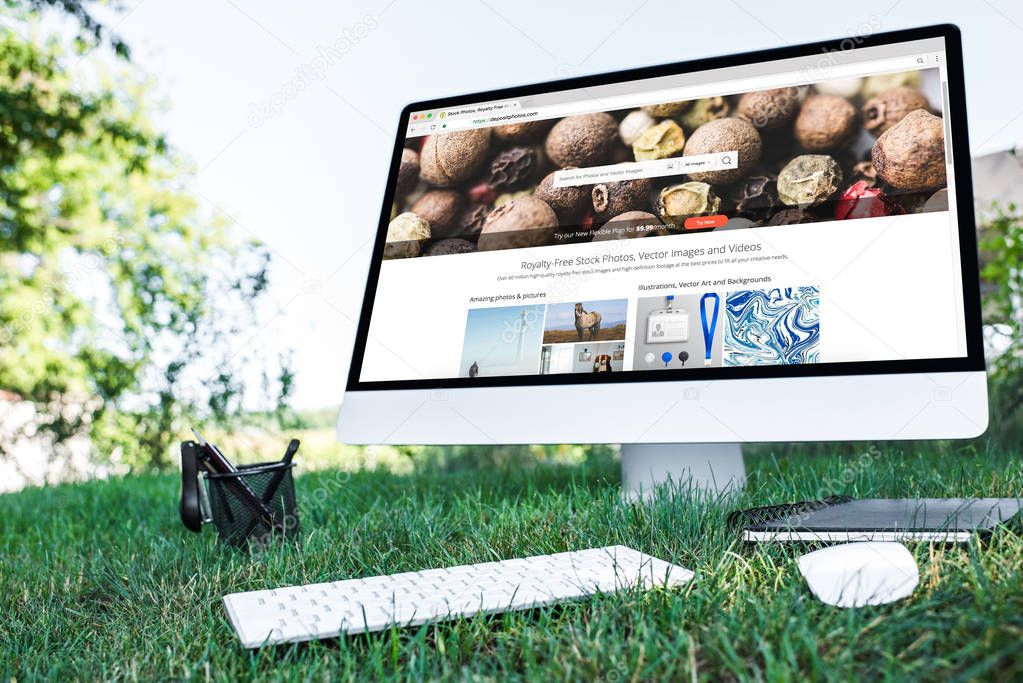 selective focus of textbook and computer with depositphotos.com website on grass outdoors