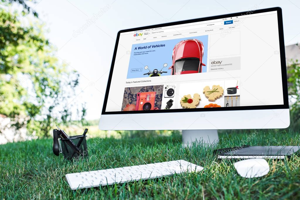 selective focus of textbook and computer with ebay website on grass outdoors