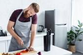 schöner lächelnder bärtiger Mann in Schürze, der per Smartphone spricht und Gemüse in der Küche schneidet