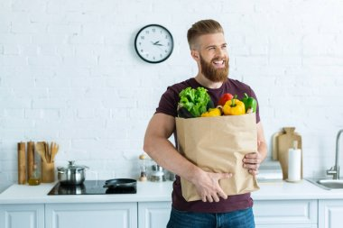 Handsome smiling young man holding grocery bag with vegetables and looking away in kitchen stock vector