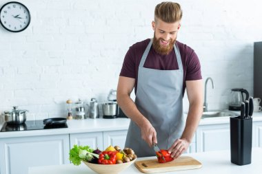 handsome smiling young man in apron cutting bell pepper on wooden cutting board
