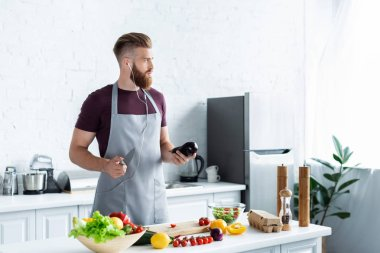 handsome bearded man in apron listening music in earphones and looking away while cooking in kitchen