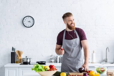 handsome smiling bearded man in apron listening music in earphones and looking away while cooking in kitchen