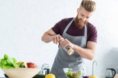 handsome smiling young man in apron spicing vegetable salad