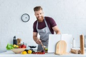handsome bearded man in apron cooking vegetable salad and smiling at camera