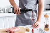 Fotografie cropped shot of man in apron pouring red wine while cooking steak