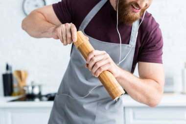cropped shot of smiling bearded man in apron listening music in earphones while cooking in kitchen