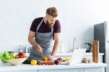 handsome bearded man in apron using laptop and cooking vegetable salad