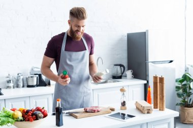 handsome smiling bearded man in apron cooking delicious steak in kitchen