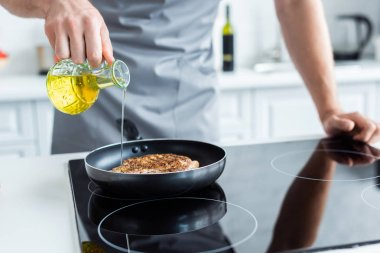 cropped shot of man in apron pouring oil while cooking steak on frying pan