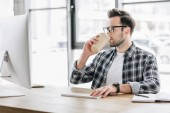 Fotografia young man in eyeglasses drinking coffee from paper cup and using desktop computer
