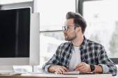 Fotografia bello giovane programmatore in occhiali prendere appunti e lavorare con computer desktop