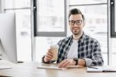 pohledný mladý programátor drží pohárek a usmívá se na kameru při sezení na pracovišti