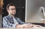Fotografia giovane sorridente in occhiali utilizzando computer desktop al posto di lavoro
