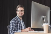 handsome smiling young programmer in eyeglasses working with desktop computer