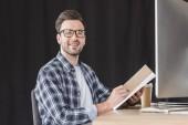 pohledný mladý muž v brýlích zapisování poznámek v poznámkovém bloku a usmívá se na kameru při sezení na pracovišti