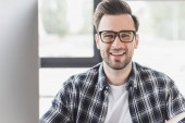 Fényképek csinos, fiatal férfi a szemüvegek mosolyogva kamera munkahelyen portréja