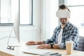 Fényképek mosolygó fiatal ember a munkahelyen asztali számítógép segítségével virtuális-valóság sisak