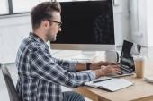 Fotografie boční pohled na usmívající se mladý muž v brýlích pomocí přenosného počítače na pracovišti