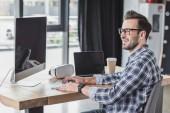 usměvavý mladý muž v brýlích pomocí stolního počítače a notebooku na pracovišti