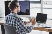 mladý muž v brýlích drží pohárek při práci s notebooky a stolní počítače