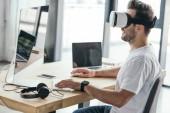 Fotografia giovane uomo sorridente in cuffie da realtà virtuale utilizzando computer desktop al posto di lavoro